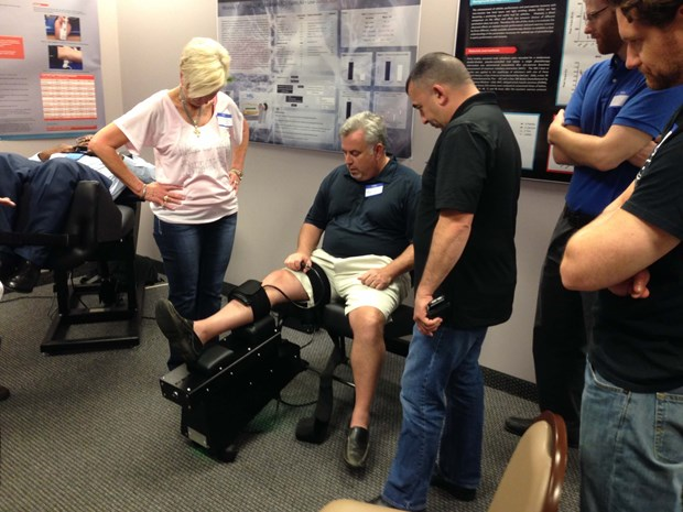 Back on Trac CEO Linda Anderson helps an attendee try out the Knee on Trac System